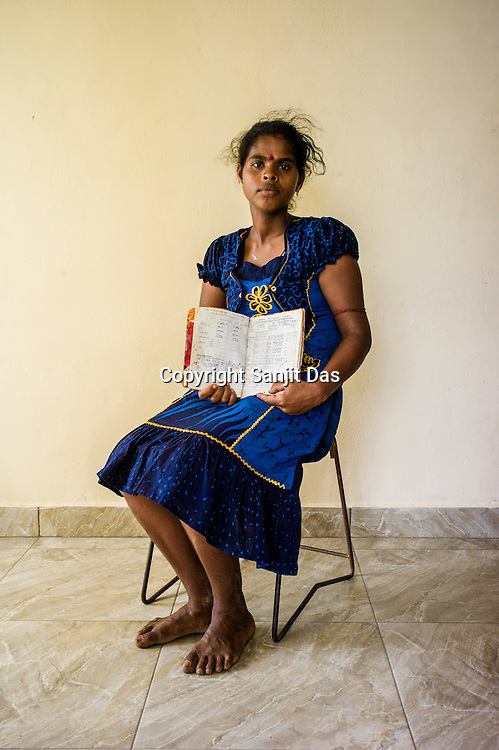 A Sri Lankan woman poses for a photo with her children and the CHDR- Child Health Development Record Card (immunization/vaccination card) in the Ministry of Health office in Tharmapuram Village in Kilonochchi, Sri Lanka.  Photo: Sanjit Das/Panos