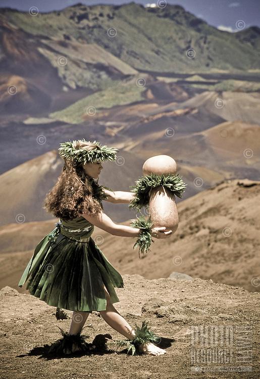 Native woman dancing hula with ipu (gourd) at Haleakala crater, island of Maui