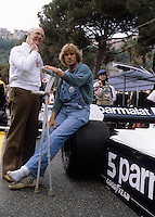 Unknown date or location. James Hunt, holding crutches, sitting next to TV Commentator Murray Walker. Walker passed away at the age of 97 on 13th March 2021