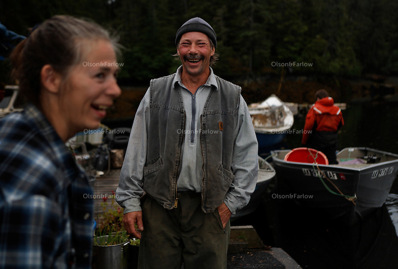 Shirley Ecklund has lived 12 years in a  float house where transportation is only by boat or float plane.  She and a friend share a joke on the dock of her home.