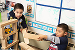 Education preschool 4 year olds two boys playing with structure they made from wooden blocks, vehicles inside structure