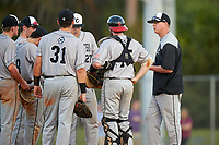 Northeastern Huskies head coach Mike Glavine (right) makes a mound visit during a game against the South Dakota State Jackrabbits on February 23, 2019 at North Charlotte Regional Park in Port Charlotte, Florida.  Northeastern defeated South Dakota State 12-9.  (Mike Janes/Four Seam Images)