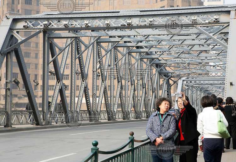 Tourists take their own picture in front of the Waibaidu Bridge in Shanghai. The 105 year old bridge, one of the oldest steel bridges in China, will be dismantled and rebuilt as part of the 110 billion Yuan (11 billion Euros) transportation upgrade plan for the city in preparation for the 2010 Expo.