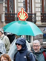 Nederland -  Amsterdam - 10 Maart 2019.  De Klimaatmars. De protestmars trekt in de stromende regen door het centrum van Amsterdam. Shell logo met opgestoken middelvinger.  Foto Berlinda van Dam / Hollandse Hoogte