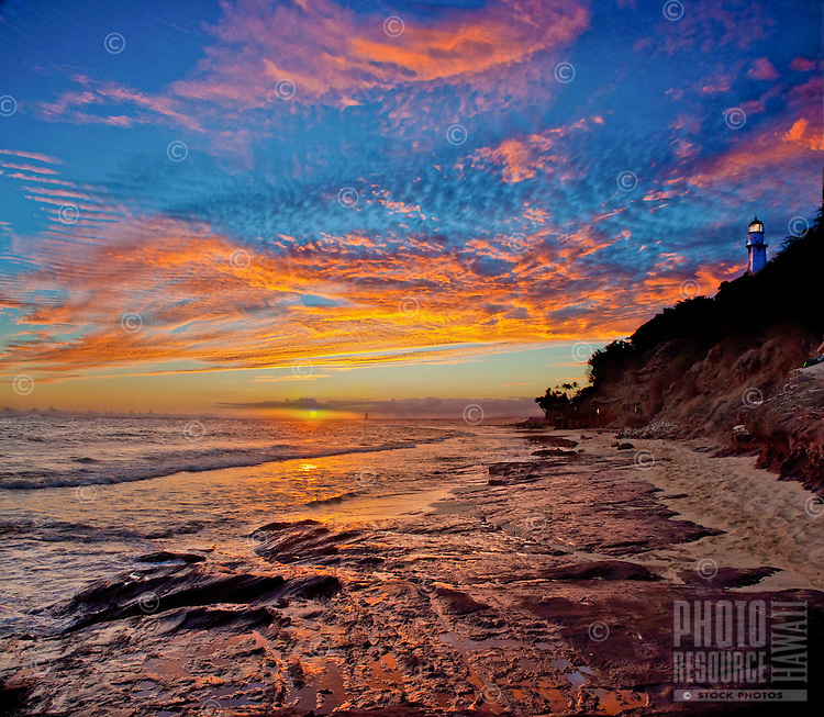 A magnificent sunset lights up the sky and ocean at the beach park below the Diamond Head Lighthouse, Honolulu, O'ahu.