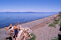 "People sunbathing on the Beach and swimming and wading in the Pacific Ocean at Qualicum Beach, in the ""Oceanside Region"" of Vancouver Island, British Columbia, Canada"