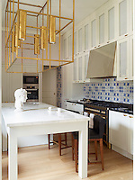 Achille Salvagni designed the brass light fixture in this contemporary kitchen. The custom- made cabinetry is painted in Farrow & Ball's Elephant's Breath, and the walls are painted in Skimming Stone.