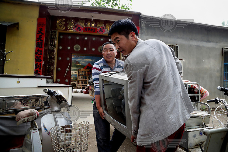 A 29 year old man moves his family out of a village accommodation for his new urban home after his old village house was bulldozed by the government to build high-rise in Liaocheng city in the northeastern Chinese province of Shangdong. In the four years between his rural home being razed and the completion of the new city apartment, Fu and his family lived in temporary housing such as this one. The Chinese government plans to move 250 million rural residents into urban areas over the coming dozen years though it is unclear whether people want to move and where the money for this project will come from. Further urbanisation is meant to drive up consumption to counterbalance an export orientated economy and end subsistence farming but the drive to get people off the land is causing tens of thousands of protests each year. /Felix Features