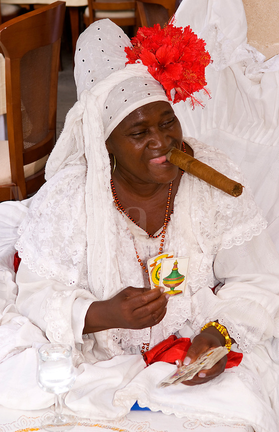 Woman with big cigar reading tallow cards of Santeria Religion cult dressed in white in Havana Cuba Habana
