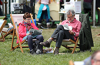 Monday 26 May 2014, Hay on Wye, UK<br /> Pictured: A man and a woman reading books sitting on deck chairs on the green.<br /> Re: The Hay Festival, Hay on Wye, Powys, Wales UK.