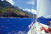 Woman looking at seacliffs of Kauai's Na Pali Coast from deck of sailing yacht