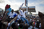 """© Remi OCHLIK/IP3 - Port au Prince on 2010 november 28 - PORT-AU-PRINCE Haiti's elections ended in confusion on Sunday as 12 of the 18 presidential candidates denounced """"massive fraud"""" and called for cancellation of the results as street protests erupted over voting irregularities.  Us singer Wyclef Jean, and Haitian presidential candidates, Michel Martelly and Charles Henry Baker demonstrate on the roof top of a SUV among a crowd of their supporters"""