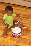12 month old baby boy sitting on floor hitting toy drum with drumsticks