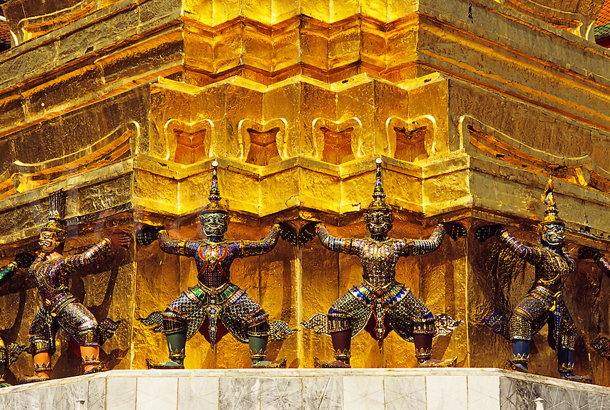 Wat Phra Keo, Bangkok, Thailand.  Demons figures supporting a gold leaf covered stupa. Royal Palace or Temple of the Emerald Buddha.