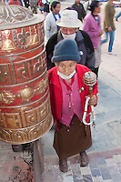 Bodhnath, Nepal.  Nepalese Woman Circumambulating the Stupa Stops to Spin Large Prayer Wheel.  She spins a portable prayer wheel in her hand.  She wears a breathing mask because of heavy air pollution.