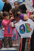 """Meta Stevenson holds her prize winning """"OB Love & Peace"""" kite while speaking to her daughter Ava during the 60th annual Ocean Beach Kite Festival, Craft Fair and Parade on Saturday, March 1, 2008.  Stevenson won for """"Best Theme"""" in the adults competition."""