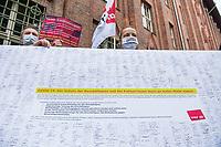 """Unter dem Motto """"Geld fuer Pflege statt fuer Autos! - Klimabewegung & Pflegekraefte fuer einen Corona-Krankenhaus-Pakt"""" protestierten am Freitag dem 29. Mai 2020 in Berlin vor der Senatsverwaltung fuer Gesundheit ca. 50 Menschen. Sie forderten, statt Milliardenbetraege an Corona-Hilfen an die Flug- und Autoindustrie zu geben, die Angestellten im Gesundheitsbereich und Krankenhaeusern zu unterstuetzen.<br /> Im Anschluss an die Kundgebung verhandelten Krankenhaussbeschaeftigte mit der Gesundheitssenatorin Kalayci ueber ihre Forderungen nach einem Corona-Krankenhaus-Pakt, der von mehr als 4.000 Berliner Beschaeftigten mit Unterschrieben wurde. Der Gesundheitspakt beinhaltet Forderungen wie die Wiedereingliederung der outgesourcten Beschaeftigten, eine verbindliche Personalbemessung, die Abschaffung der Fallpauschalen und ein besserer Gesundheitsschutz fuer die Mitarbeiter.<br /> Im Bild: Mitglieder der Dienstleistungsgewerkschaft ver.di halten ein Plakat mit den Unterschiften.<br /> 29.5.2020, Berlin<br /> Copyright: Christian-Ditsch.de<br /> [NUR FUER REDAKTIONELLE ZWECKE! Werbung nur auf Anfrage beim Fotografen. Inhaltsveraendernde Manipulation des Fotos nur nach ausdruecklicher Genehmigung des Fotografen. Vereinbarungen ueber Abtretung von Persoenlichkeitsrechten/Model Release der abgebildeten Person/Personen liegen nicht vor. NO MODEL RELEASE! Don't publish without copyright Christian-Ditsch.de, Veroeffentlichung nur mit Fotografennennung, sowie gegen Honorar, MwSt. und Beleg. Konto: I N G - D i B a, IBAN DE58500105175400192269, BIC INGDDEFFXXX, Kontakt: post@christian-ditsch.de<br /> Bei der Bearbeitung der Dateiinformationen darf die Urheberkennzeichnung in den EXIF- und  IPTC-Daten nicht entfernt werden, diese sind in digitalen Medien nach §95c UrhG rechtlich geschuetzt. Der Urhebervermerk wird gemaess §13 UrhG verlangt.]"""
