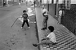 Mazatlan Mexico. Children playing a violent game in the street, boys wearing typical Mexican wrestling masks. No doubt influenced by watching to much TV.  1973. 1970s