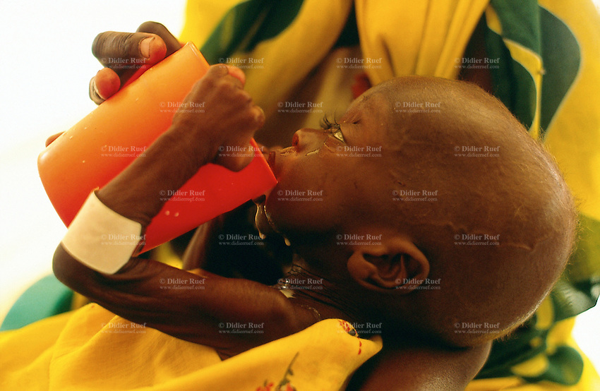 Sudan. West Darfur. Habilah. The non-governmental organization (ngo) Médecins sans Frontières (MSF) Switzerland runs an ambulatory therapeutic feeding center (TFC) for malnourished children. A young boy in his mother's arms drinks milk from an orange cup. © 2004 Didier Ruef