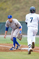 Brandon Dulin (26) of the Burlington Royals waits for a throw as Gianfranco Wawoe (7) hustles down the first base line at Calfee Park on June 20, 2014 in Pulaski, Virginia.  The Mariners defeated the Royals 6-4. (Brian Westerholt/Four Seam Images)