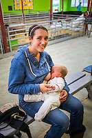 """A mother breastfeeding her baby of eight months in a barn at a visitor farm park with chicken incubators in the background.<br /> <br /> Image from the breastfeeding collection of the """"We Do It In Public"""" documentary photography picture library project: <br />  www.breastfeedinginpublic.co.uk<br /> <br /> <br /> Gloucestershire, England, UK<br /> 30/09/2013<br /> <br /> © Paul Carter / wdiip.co.uk"""