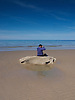 A West Wales beach in summer when at low tides the warm coastal winds can slowly create patterns in the sand and a lone walker relaxes sitting on a rock and contemplating and enjoying the view.<br /> <br /> Stock Photo by Paddy Bergin