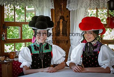 Deutschland, Baden-Wuerttemberg, Ortenaukreis, Kirnbach (Wolfach): zwei junge Frauen sitzen in einer Schwarzwaldstube mit der beruehmten Tracht mit dem roten und schwarzen Bollenhut, die heute in der ganzen Welt als Schwarzwaelder Tracht bekannt ist | Germany, Baden-Wurttemberg, Kirnbach (Wolfach): two young women posing in famous Black Forest costume with red and black Bollenhat in living room of a Black Forest house