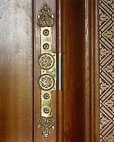 An ornamental brass hinge adorns a wooden door