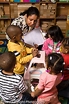 Day Care Center teacher holding clipboard on which she writes observations on the children working with group of 2 year olds vertical