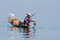 Myanmar, Burma.  Fisherman Laying out his Net, Inle Lake, Shan State.