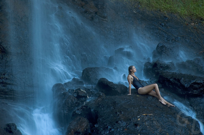 A Girl relaxes under the biggest waterfall in Palau Micronesia, the fall is surrounded by lush jungle a favorite spot for locals and tourist, but a one hour hike.