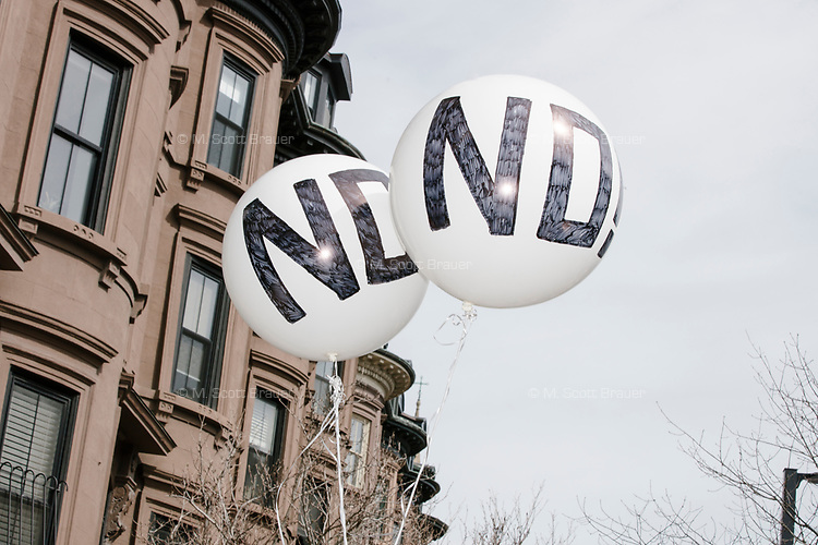 """Balloons reading """"No!"""" are seen in front of houses as people take part in the March For Our Lives protest, walking from Roxbury Crossing to Boston Common, in Boston, Massachusetts, USA, on Sat., March 24, 2018, in response to recent school gun violence."""