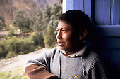 Ollantaytambo, Peru. Peruvian Andean Indian Quechua boy looking out of a window.