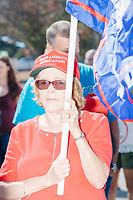 A woman wears a Make America Great Again hat and holds a Trump flag as alt-right organization Super Happy Fun America demonstrates against facemasks, vaccines, and pandemic closures, and in support of the reelection of President Donald J. Trump near the residence of Massachusetts governor Charlie Baker in Swampscott, Massachusetts, on Sat., Sept. 26, 2020. Super Happy Fun America is most well known for organizing the Straight Pride Parade in Boston on August 31, 2019.