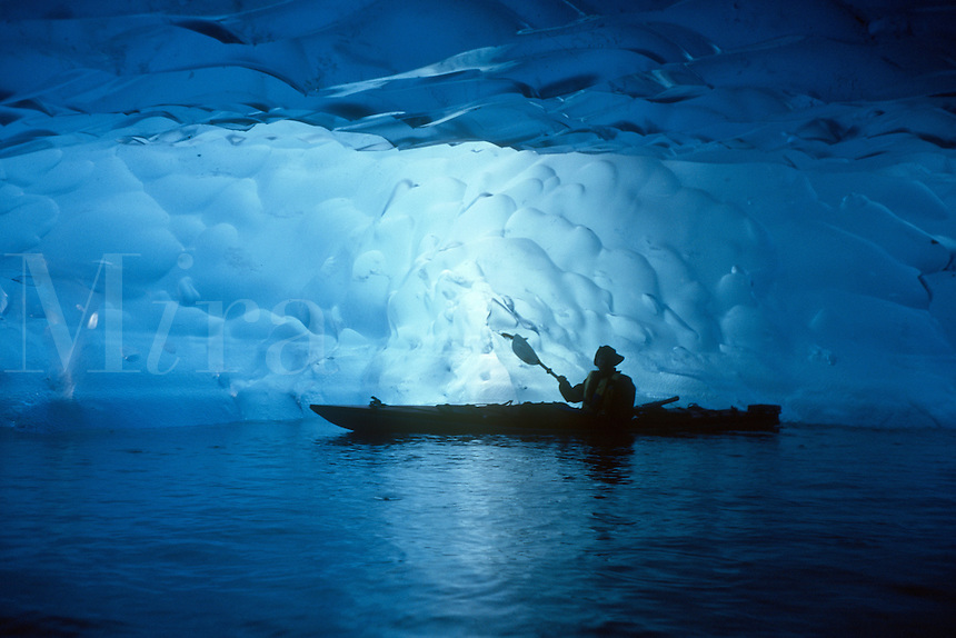 A kayaker paddles his sea kayak through an ice cave in the face of the Mendenhall Glacier in southeast Alaska. M