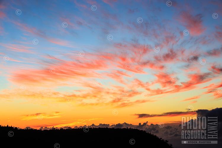 Sunset creates a brilliantly colored sky over the Pu'u o Kila Lookout and the Pihea Trail, Kaua'i.