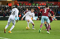 Pictured: Gylfi Sigurdsson of Swansea, team mate Modou Barrow (L) and Aaron Cresswell of West Ham (R) Saturday 10 January 2015<br /> Re: Barclays Premier League, Swansea City FC v West Ham United at the Liberty Stadium, south Wales, UK