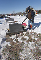 SEEKING SOLID GROUND<br />Mark Malugen (cq) with Bentonville Public Works department blows snow Tuesday Feb. 16 2021 from a burial plot at the Bentonville Cemetery, 400 S.W. F St. A crew removed snow to dig a grave for a woman who passed away at age 107, Malugen said. Go to nwaonline.com/210217Daily/ to see more photos. <br />(NWA Democrat-Gazette/Flip Putthoff)