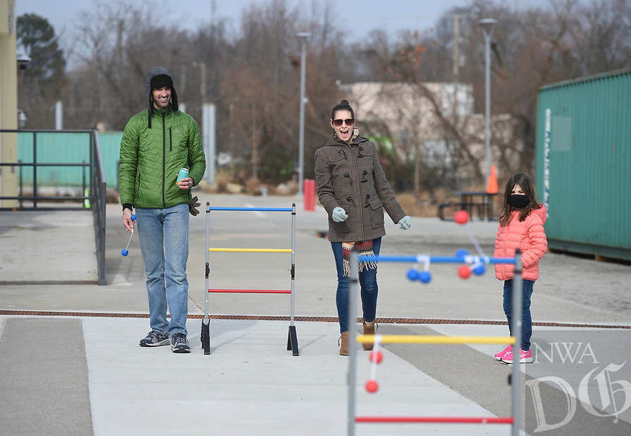 Garrett Brewer (from left), Laura Brewer and Lillian Brewer, 5, of Bentonville play ladder ball, Sunday, January 10, 2021 at The Momentary grounds in Bentonville. The Momentary hosted a free outdoor pop-up experience called Winter Glow. Attendees enjoyed games, food and pits. Check out nwaonline.com/210111Daily/ for today's photo gallery. <br /> (NWA Democrat-Gazette/Charlie Kaijo)