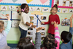 Education Preschool 4 year olds two girls posing as teachers, group of children as ther class