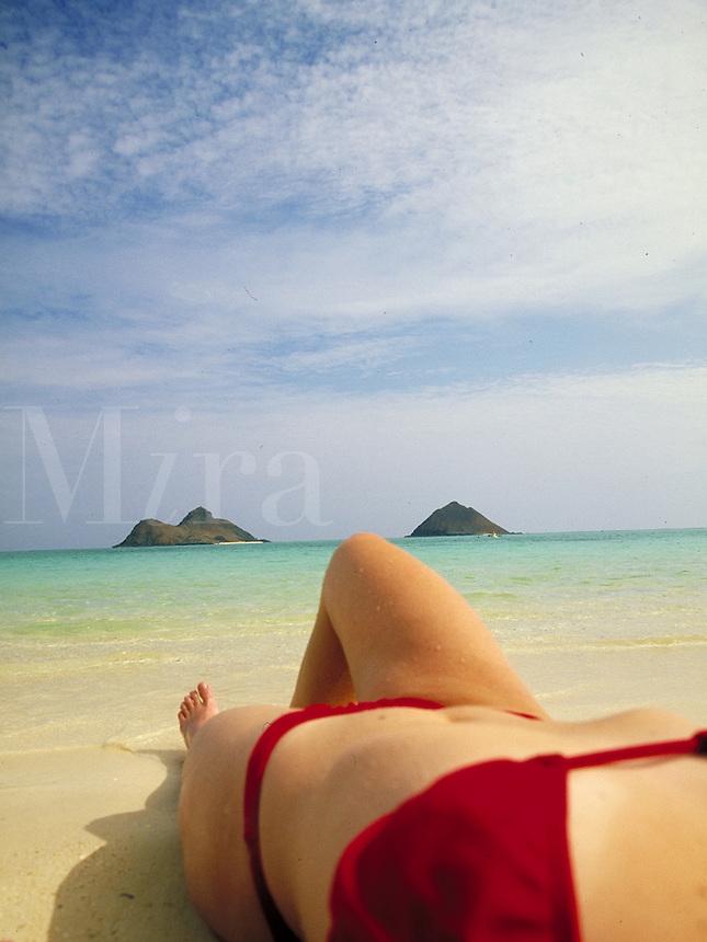 Young woman in a bikini sunbathing on a tropical beach. close up from behind, seascape, model. Lori Pigeon. Hawaii.