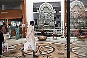 Family members of the patients and other visitors walk past a HIndu God's statue in the waiting lounge of the Narayana Hrudayalaya in Bangalore, Karnataka, India. Photo: Sanjit Das/Panos