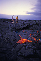 Two men on a lava field viewing molten lava, Volcanoes National park