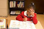 K-8 Parochial School Bronx New York Kindergarten girl working in math workbook horizontal covering eyes with hand playful