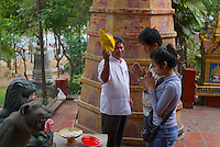 "A young couple offering raw meat at Wat Phnom ""Mountain Pagoda"") is a Buddhist Temple located in Phnom Pen, Cambodia. It was built in 1373, and stands 27 meters (88.5 ft) above the ground. It is the tallest religious structure in the city. The pagoda was given the name of Wat Preah Chedey Borapaut."