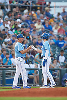 Omaha Storm Chasers Bobby Witt Jr. (7) and manager Brian Poldberg (27) during a game against the Iowa Cubs on August 14, 2021 at Werner Park in Omaha, Nebraska. (Zachary Lucy/Four Seam Images)
