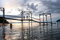 Malawi, Cape Maclear. Children jumping from the pier at sunste.