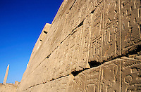 Wall full of hieroglyphs and an obelisk at the Karnak Temple Complex in Luxor, Egypt.