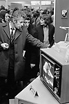 New Year sales, department store selling cheaper televisions. Two men make customers making a decision. 1970s London UK