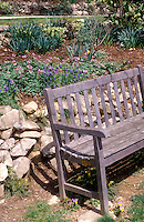 Wooden bench against retaining wall with spring bulbs and flowers 29373